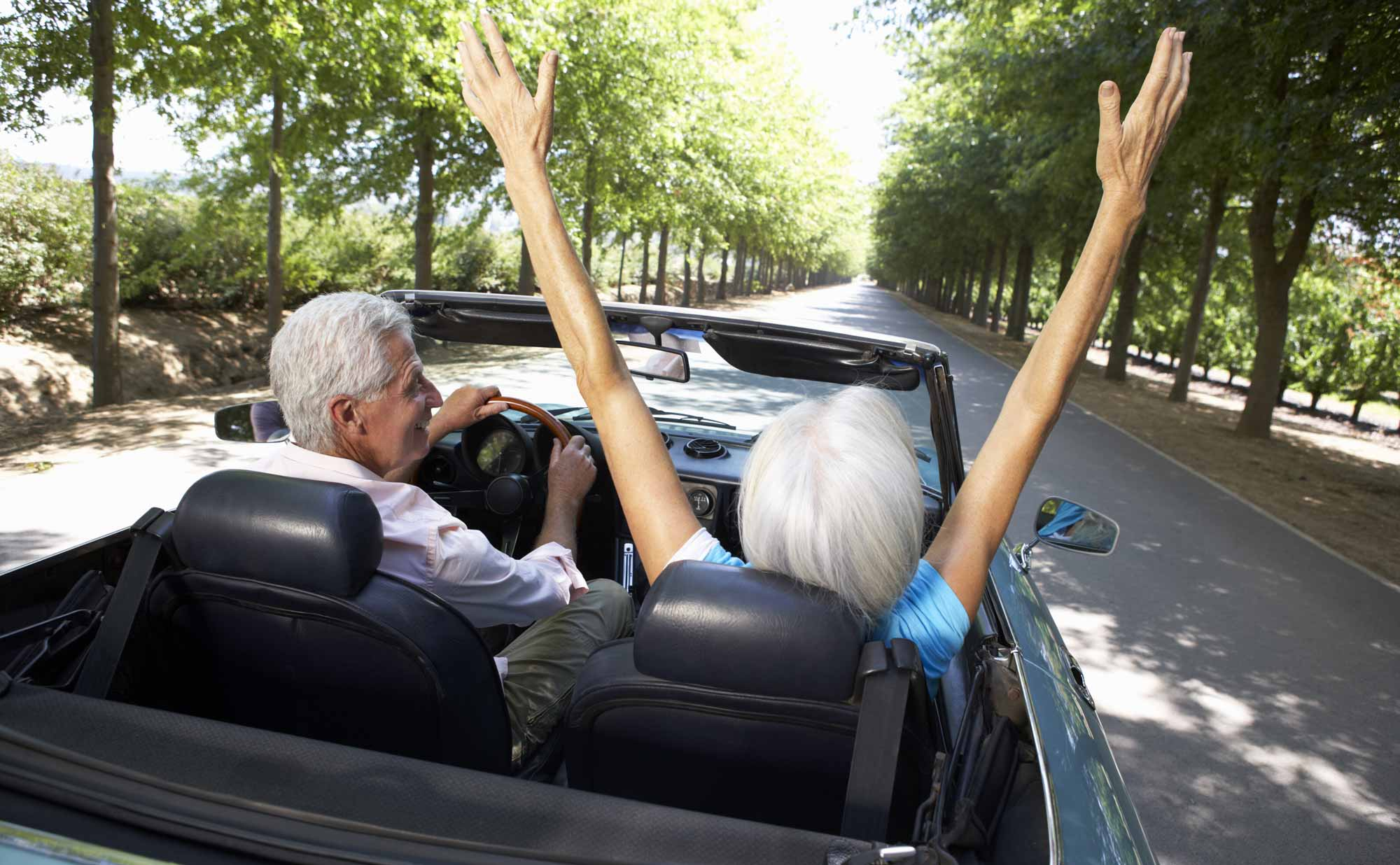 happy couple celebrating retirement in convertible
